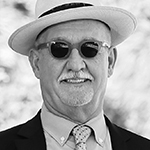 BW image of Tim Schmand in a hat and sun glasses