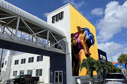 Image of the outside of the building with a large panther mural painted on a large wall and an FIU sign above a skybridge. The door has Mana on one side and FIU on the other in raised letters.